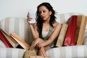 A woman sitting on a sofa with shopping bags